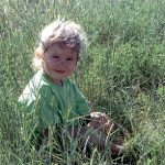 Child sitting in rye grass
